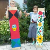 Kinder zeigen stolz ihre bemalten Bretter