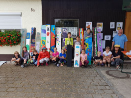 Die Kinder zeigen ihre bunten Produkte. Rechts im Bild Irene Schinkel und Dieter Teufel.