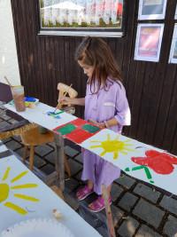 Malerkittel schützen die Kleidung der Kinder.