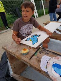 Ein Junge vertieft sich in Details seines Gemäldes.